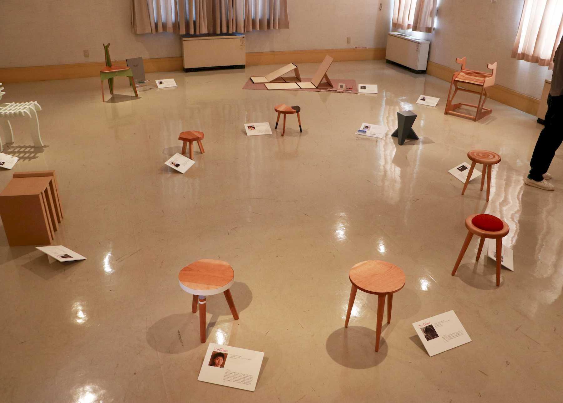 展示会の様子:円陣を組む小型の背もたれ無し椅子7脚が本学学生作品です