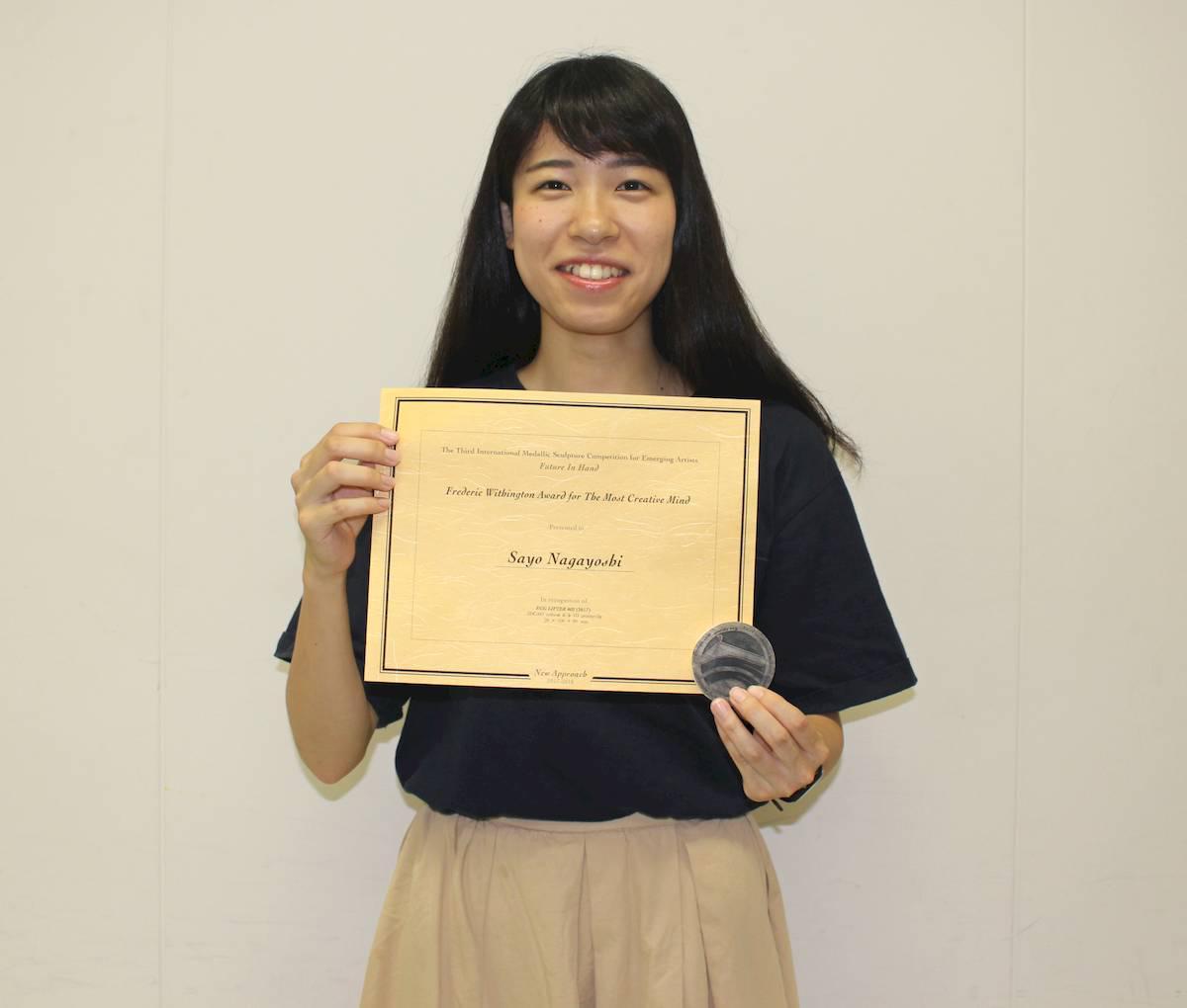 賞状と記念品のメダルを手に受賞を喜ぶ永吉さん