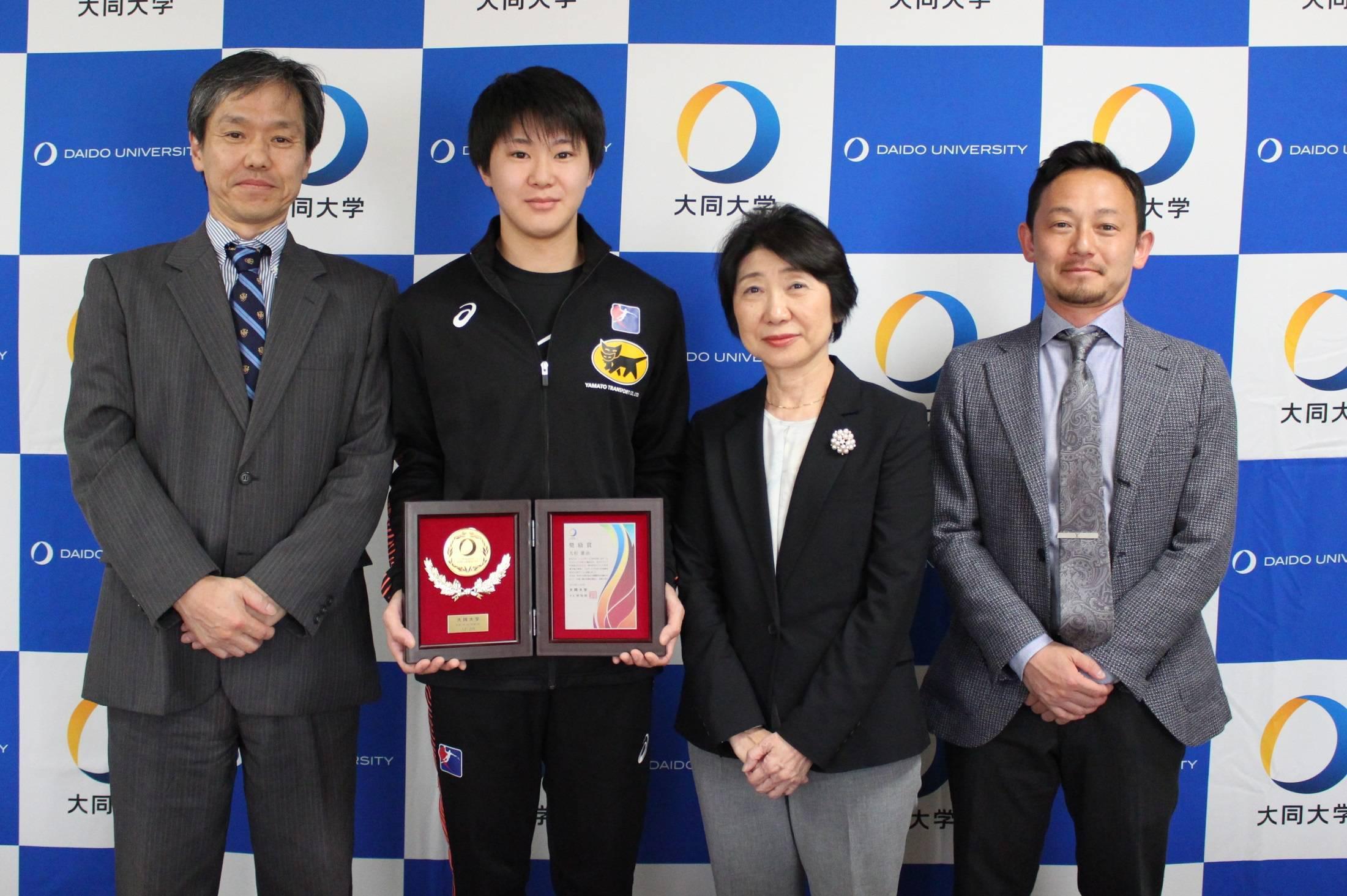 授与式の様子(左から、高田学生部長、大杉さん、神保学長、伊藤学生部次長)