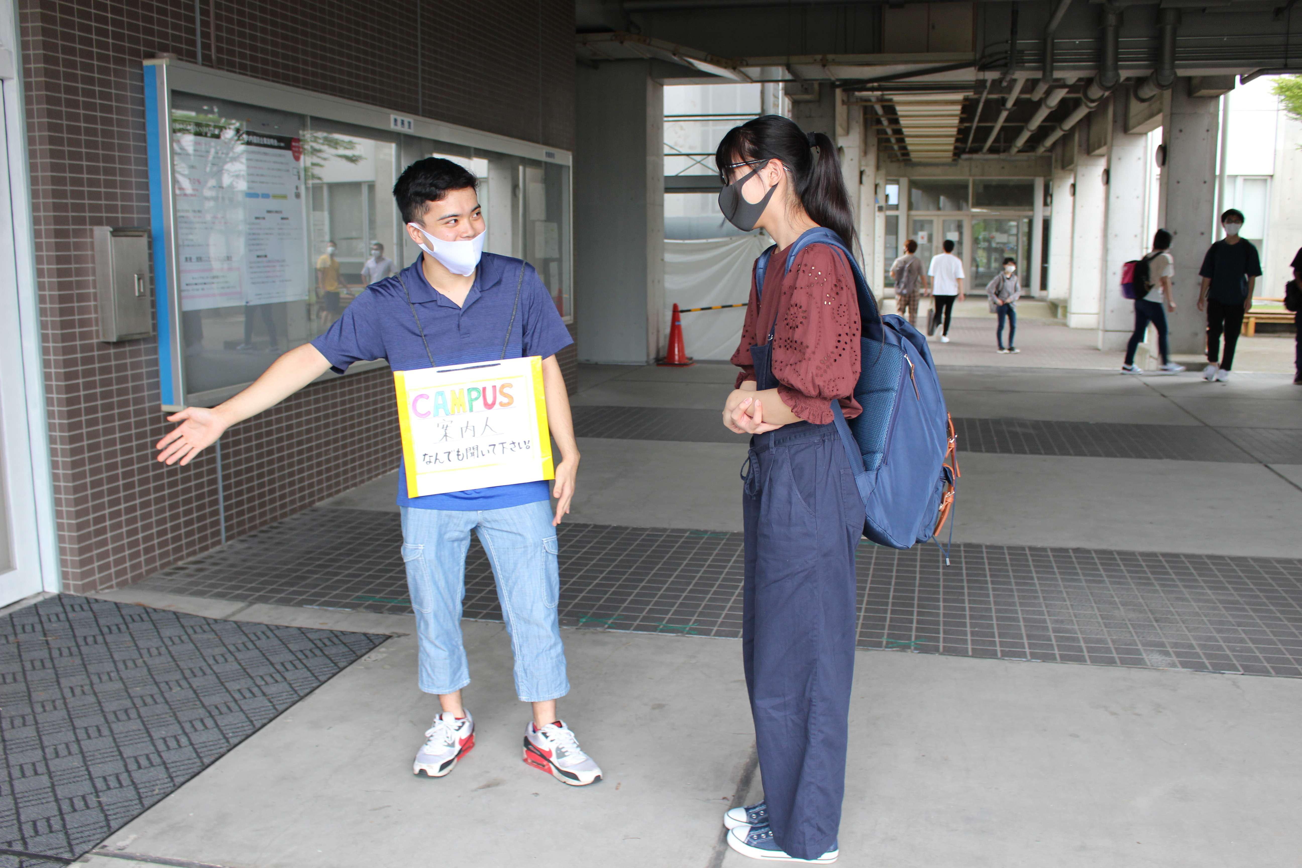 新入生に声掛けする岩崎さん(左)